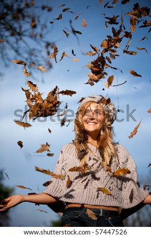 Beautiful autumn woman with leaves falling from the tree - stock photo