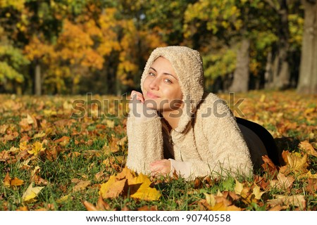 Beautiful autumn woman with leaves in park. Outdoor shot - stock photo