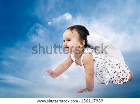 Beautiful Baby angel sitting on the clouds