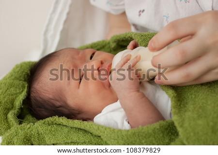 Beautiful Baby Asian Girl being Fed Formula - stock photo
