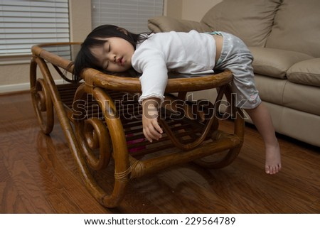 Beautiful baby asian toddler girl falls asleep on bamboo table
