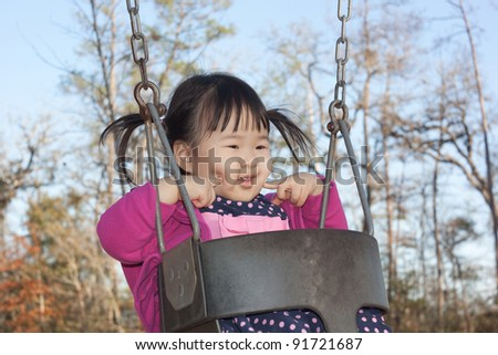 Beautiful baby asian toddler girl making cute face while riding swing set