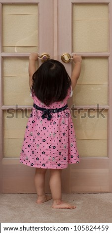 Beautiful Baby Asian Toddler Girl Standing up and trying to open wooden doors - stock photo