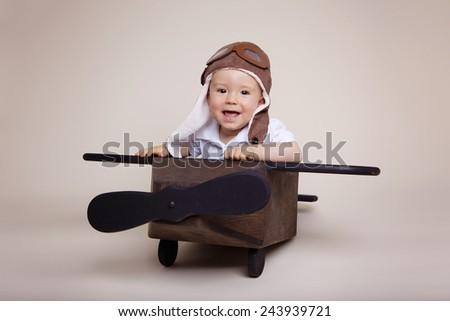 Beautiful baby boy inside a wooden airplane wearing an aviator hat - stock photo