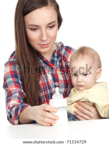 beautiful baby boy is feeding from bottle by his mother - stock photo