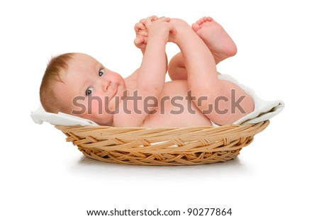Beautiful baby boy lies in pad and plays with own feet - stock photo