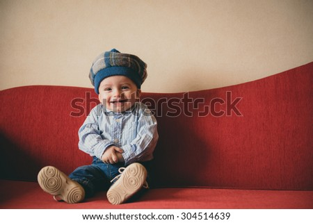 Beautiful baby boy on a red couch - stock photo