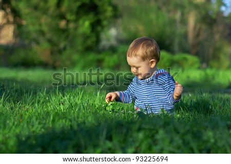 beautiful baby boy sitting among green grass on spring lawn - stock photo
