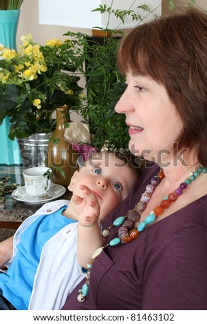 Beautiful baby boy sitting by his grandmother - stock photo