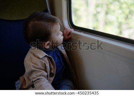 Beautiful baby boy sitting inside the train.