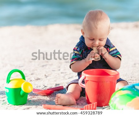 Beautiful baby boy sitting on the beach