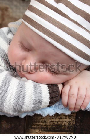 Beautiful baby boy sleeping in an antique trunk - stock photo
