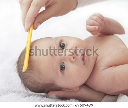Beautiful baby boy with mother combing - stock photo