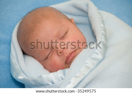 Beautiful baby boy wrapped in blue blanket - stock photo