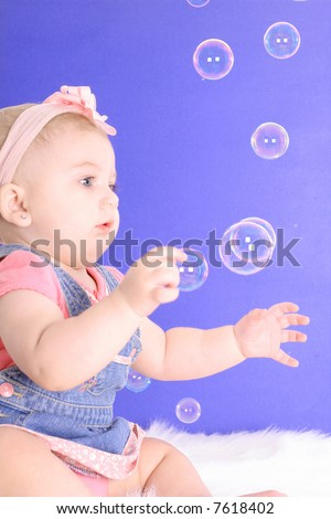 beautiful baby catching bubbles - stock photo