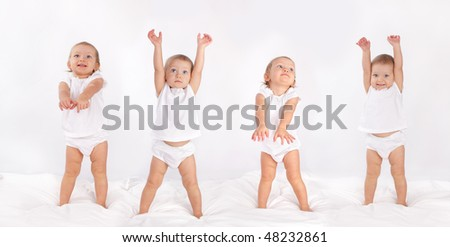 Beautiful baby dancing on bed - stock photo