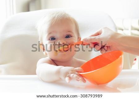 Beautiful baby eating mashed - stock photo