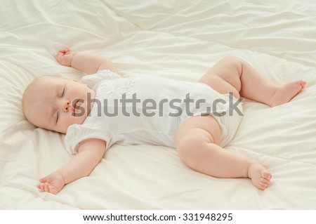 Beautiful baby girl asleep on a blanket.