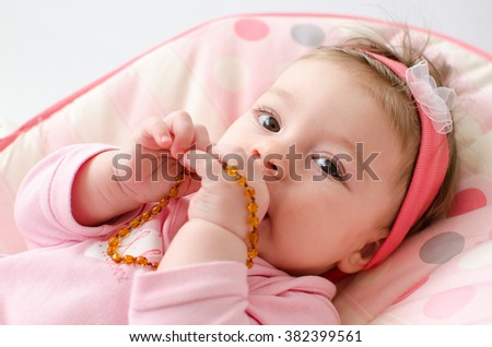 beautiful baby girl chewing amber teething necklace - stock photo