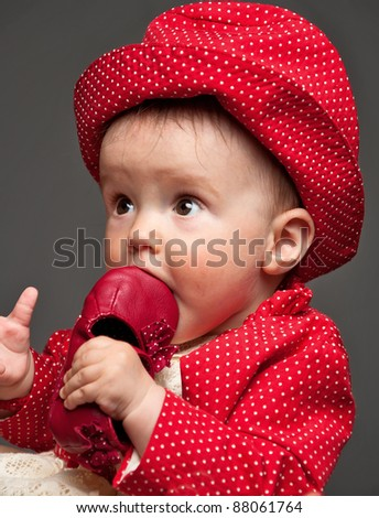 Beautiful baby girl dressed in a red dress eating her own delicious red shoe while looking very surprised - stock photo
