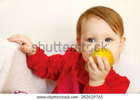 Beautiful baby girl eats red apple. - stock photo