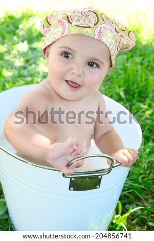 Beautiful baby girl having a bath outdoors - stock photo