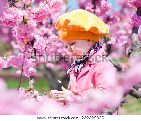 Beautiful baby girl in blooming apricot tree branches - stock photo