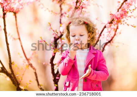 Beautiful baby girl in blooming jasmine tree branches - stock photo