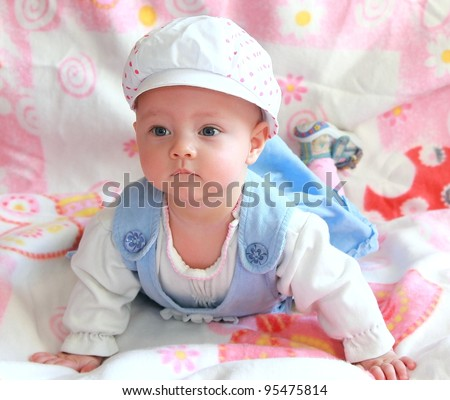 Beautiful baby girl in funny cap and blue dress lying and looking with interest - stock photo