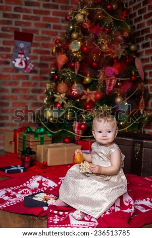beautiful baby girl in golden dress eating cookies under christmas tree - stock photo