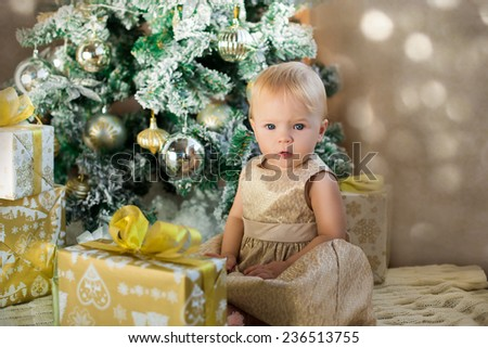 beautiful baby girl in golden dress unpacking presents under christmas tree - stock photo