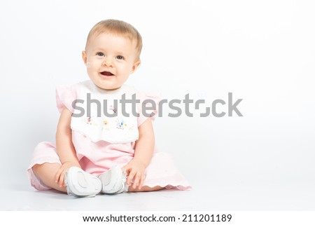 Beautiful baby girl in pink dress playing on white background