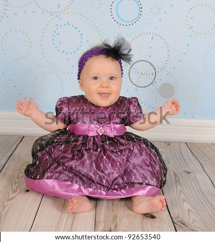 beautiful baby girl in purple dress sitting happily on floor - stock photo