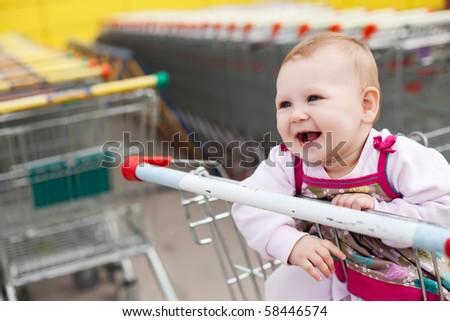Beautiful baby girl in shopping cart - trolley - stock photo