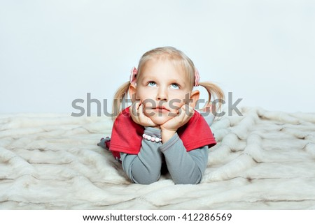 Beautiful baby girl is lying with her hands on her chin and looking up - stock photo