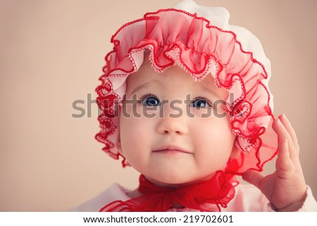 Beautiful Baby girl looking at the camera wearing read traditional Christmas hat - stock photo