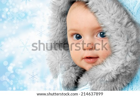 Beautiful baby girl on a snow flake background wearing a winter fur coat.  - stock photo