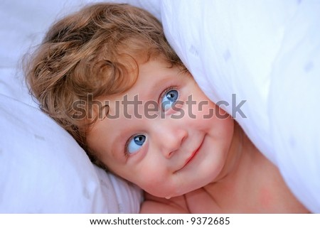 Beautiful baby girl on a white blanket - stock photo