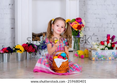 beautiful baby girl playing with Easter eggs in a room full of flowers next to a basket of eggs . A child holds out an egg in his hand - stock photo