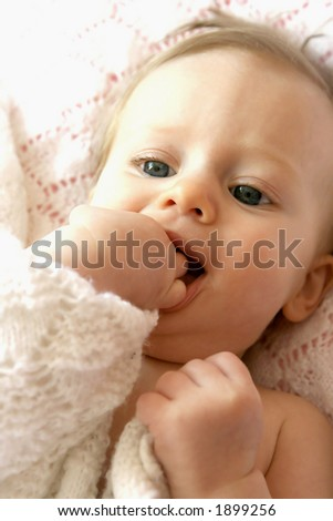 Beautiful baby girl playing with her fingers and pink blanky - stock photo