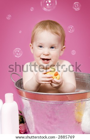 Beautiful baby girl playing with her rubber duckie in a tub - stock photo
