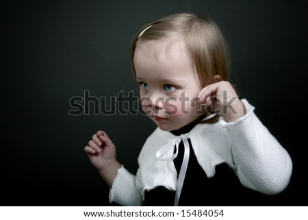 Beautiful baby girl posing on black background - stock photo