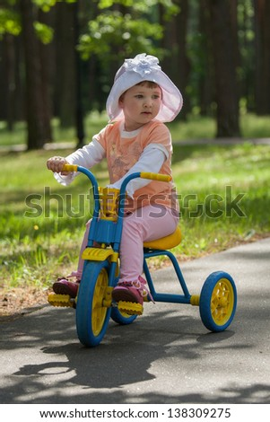 Beautiful baby girl rides tricycle in a summer park - stock photo