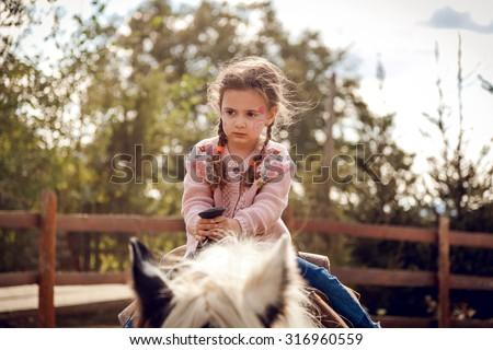 Beautiful baby girl riding horse - stock photo