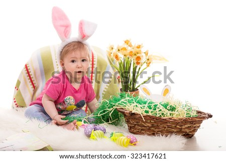 Beautiful baby girl sitting in Easter decor and wearing fluffy bunny ears - stock photo