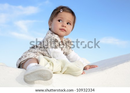 beautiful baby girl sitting on a wall smiling and having fun - stock photo