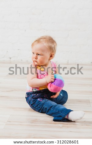 Beautiful baby girl sitting with ball in her hands