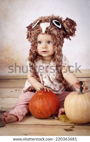 Beautiful baby girl sitting with pumpkins wearing knitted hat - stock photo
