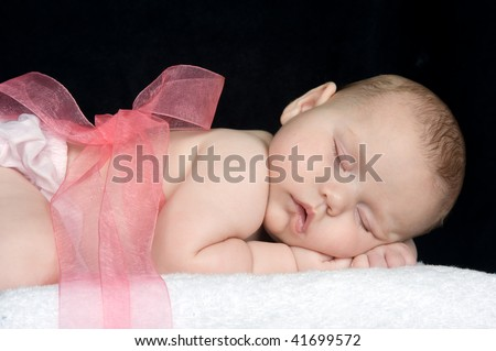 Beautiful baby girl with a pink ribbon tied around her - stock photo