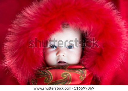 Beautiful baby girl with big blue eyes wearing a red jacket with fur hood - stock photo